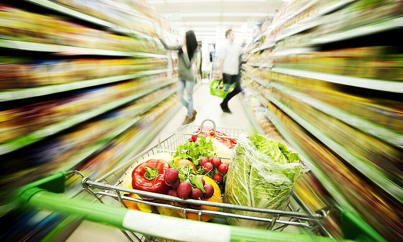 Einkaufswagen gefüllt mit Bio-Gemüse und -Produkten zwischen Regalen in einer Bio-Filiale